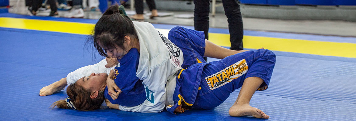 Two women engaged in a BJJ match